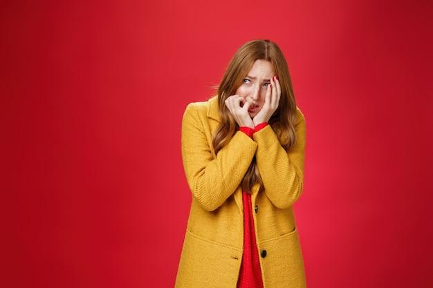 Ritratto di donna insicura scioccata e spaventata in cappotto giallo che copre il viso con orrore e paura che si morde le unghie strizzando gli occhi e guardando intensamente a sinistra come vittima di essere spaventata in piedi in tremante, tremante.