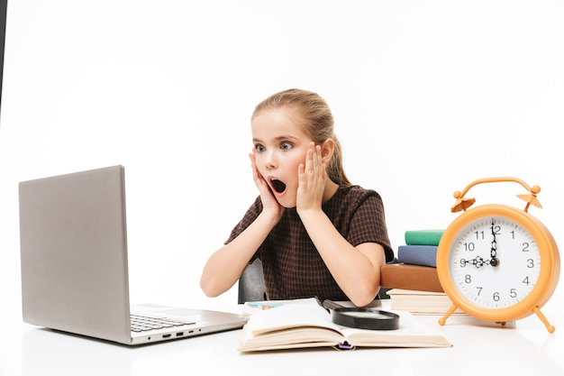 Portrait of shocked school girl using silver laptop while studying and reading books in class isolated over white wall