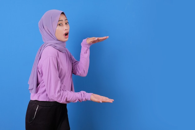 Portrait of shocked and showing young lady muslim