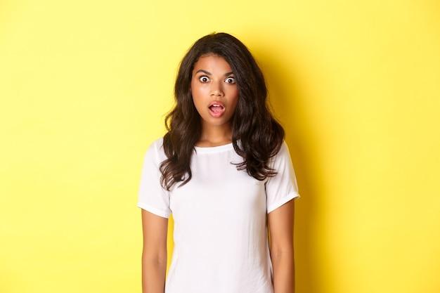 Ritratto di una ragazza afroamericana scioccata e senza parole che lascia cadere la mascella e guarda un'incredibile offerta promozionale