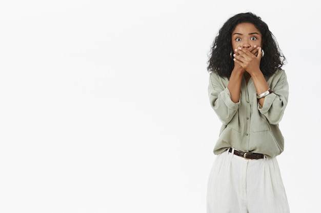 Portrait of shocked and speechless concerned african american woman with curly hair