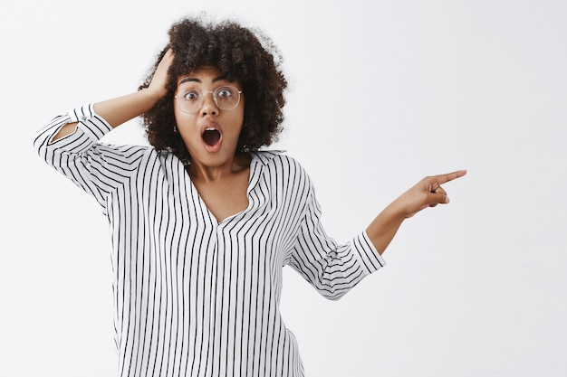 Portrait of shocked and speechless confused african american woman in glasses and striped blouse pointing right with pulled hand holding arm on head dropping jaw from shook