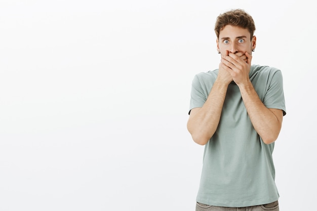 Portrait of shocked speechless handsome guy in casual t-shirt, covering mouth and staring with popped eyes, being scared and afraid