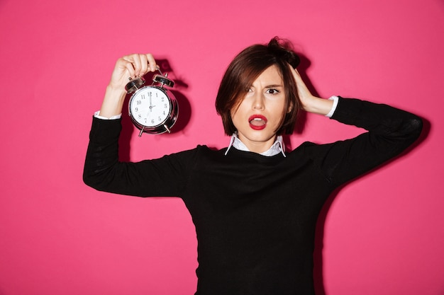 Portrait of a shocked upset businesswoman with alarm clock