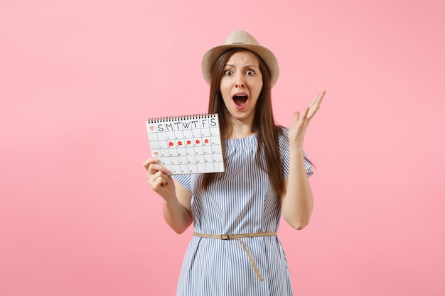 Portrait of shocked woman in blue dress, hat holding periods calendar for checking menstruation days isolated on bright trending pink background. medical, healthcare, gynecological concept. copy space
