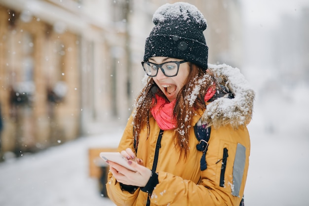 Portrait of shocked woman looking at mobile phone in hand she has some good news message photos with stunned emotion on face