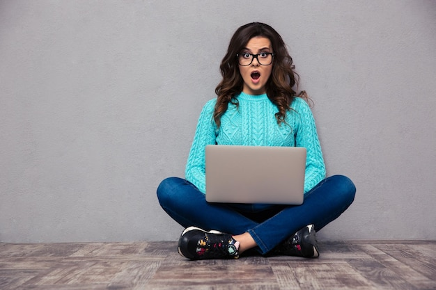 Portrait of shocked woman sitting on the floor with laptop and  on gray wall