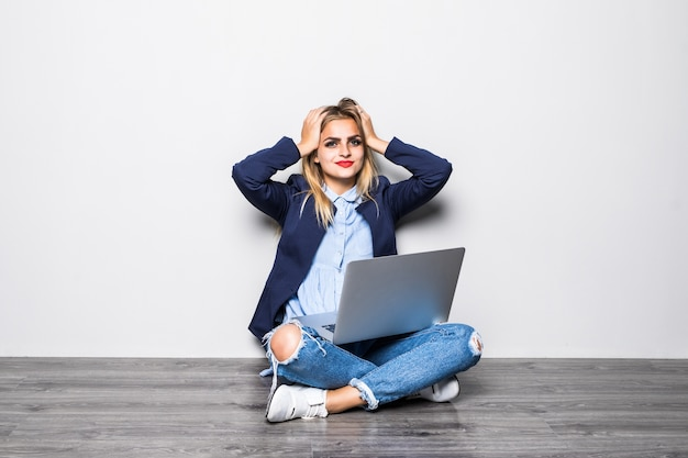 Portrait of shocked woman sitting on the floor with laptop and looking on gray wall