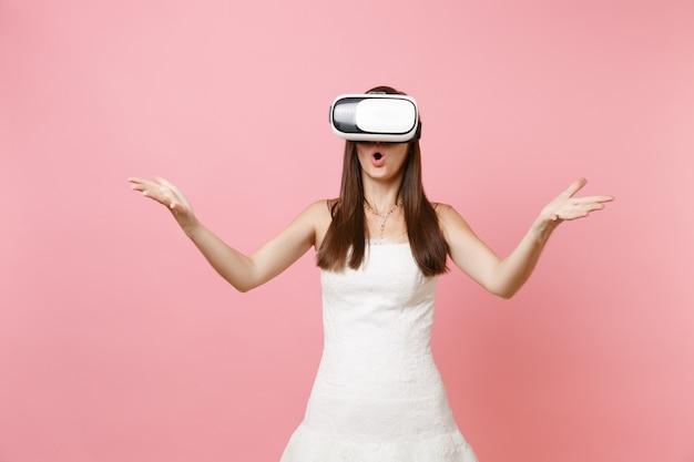 Ritratto di donna scioccata in abito bianco, cuffia di realtà virtuale che allarga le mani