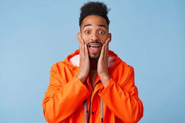 Portrait of shocked young african american dark skinned guy in orange rain coat, touches palms of cheek, can't believe that he saw his idol alive, with wide open mouth, stands.