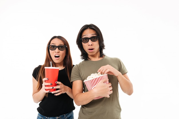 Portrait of a shocked young asian couple in 3d glasses