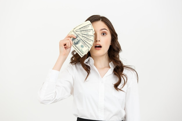Portrait shocked young business woman standing and holding money isolated over white wall.