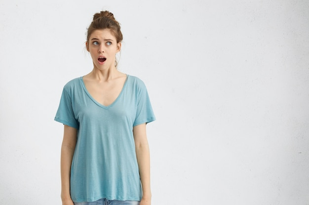 Portrait of shocked young female wearing blue shirt, having beautiful appearance