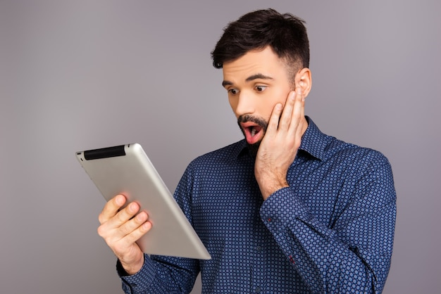 Portrait of shocked young man reading news on tablet