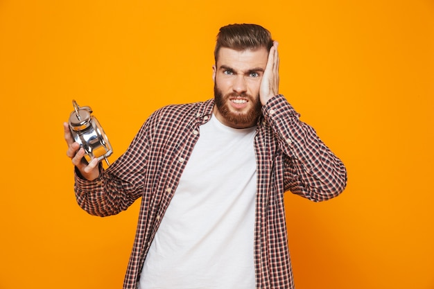 Portrait of a shocked young man wearing casual clothes holding alarm clock
