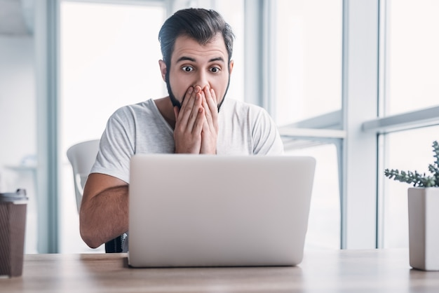 Portrait of shocked young man working on laptop computer and covering his mouth with hands