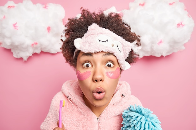 Portrait of shocked young woman has eyes popped out from wonder applies collagen patches under eyes for reducing fine lines poses with toothbrush and bath sponge models indoor