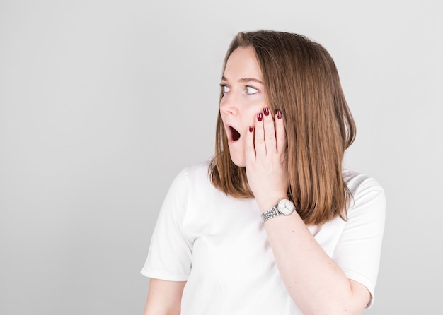 Portrait of a shocked young woman holding face with the hands over white background.