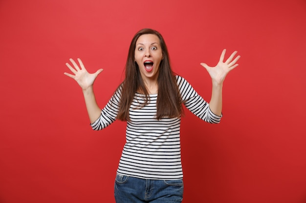 Portrait of shocked young woman keeping mouth wide open, looking surprised and spreading hands