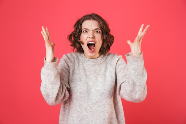 Portrait of a shocked young woman standing isolated over pink, screaming