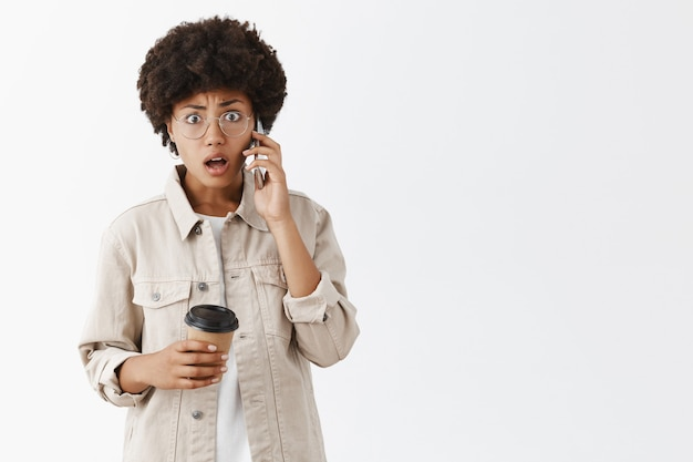 Portrait of shook confused and stunned african american female in glasses and stylish shirt, drinking coffee and talking on phone