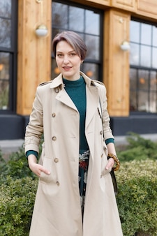 Portrait shooting of a attractive stylish short cut woman, girl walks in the city outdoors. stylish modern and feminine image, style. girl in a beige cloak or coat and a green dress
