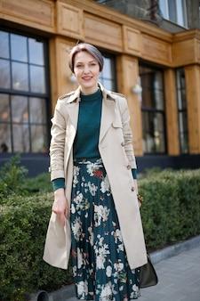 Съемка портрета привлекательной стильной короткой стрижки женщины, прогулки по городу на открытом воздухе. стильный современный и женственный образ, стиль. девушка в бежевом плаще или пальто и зеленом платье