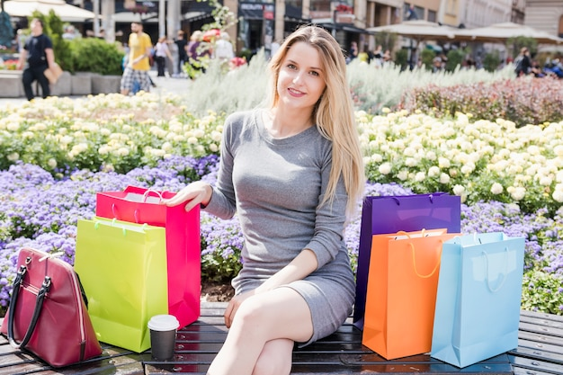 Portrait of a shopaholic woman with multi colored shopping bags