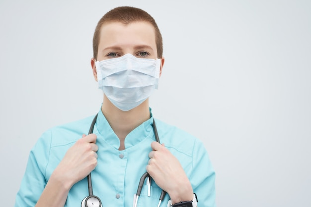 Portrait of short haircut caucasian female doctor wearing medical mask and stethoscope on neck, copy space.