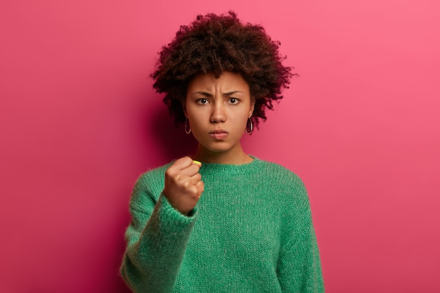Portrait of short haired angry woman shows fist, has irritated expression, promises to revenge, wears green sweater, poses against pink wall, domineers and threatens, being dissatisfied