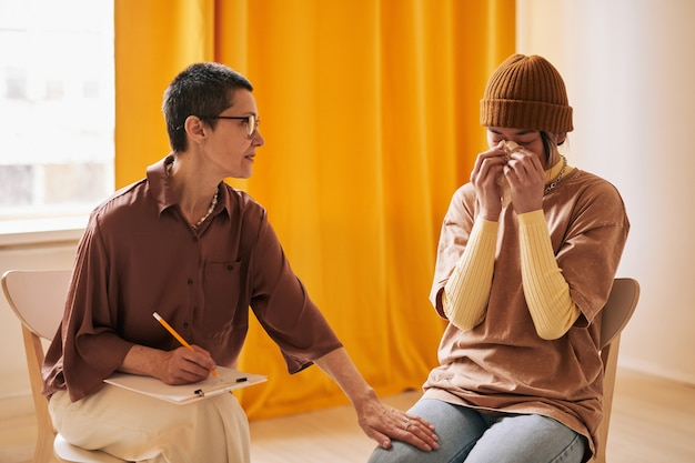 Portrait of short haired female psychologist comforting young woman crying during therapy session in support group