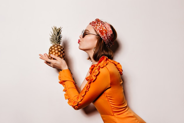 Portrait of short-haired girl in stylish hairband and orange dress kissing pineapple on white space.
