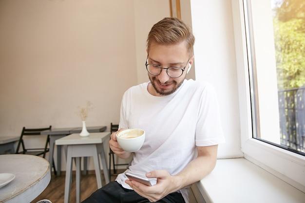 Ritratto di giovane ragazzo dai capelli corti in maglietta bianca, seduto vicino alla finestra e bere caffè, mandare sms ad un amico ed essere di buon umore
