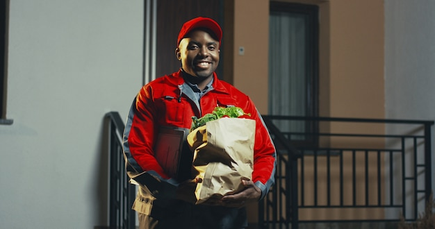 Portrait shot of the african american young man from the delivery service of supermarket in the red costume and cap with a fresh vegetables in the carton package