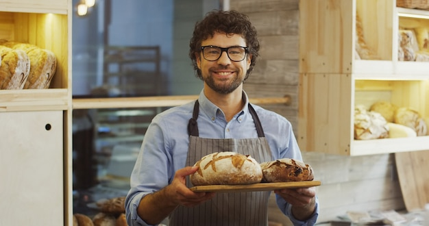 Portrait shot of the attractive young man, bakery vendor, holding a tray with fresh bread and looking at the camera with a smile. indoors