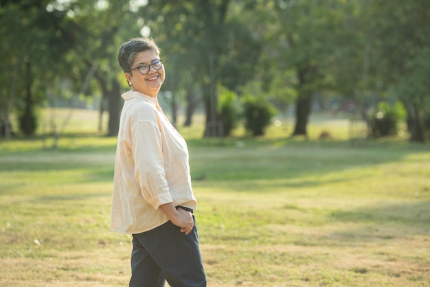 Portrait shot of happy, successful, relax caucasian senior asian woman smiling with glasses and carefree look toward the camera at the park as a background with copy space in natural autumn sunlight.
