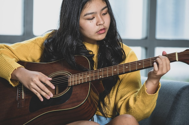 Portrait shot of an imperfect young female teenager enjoying playing the acoustic guitar. junior guitarist in yellow clothes sitting on the couch and holding an instrument with windows background