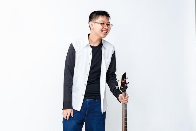 ベースギターを保持しているかわいい笑顔の少年ティーンエイジャーのポートレートショット。楽器を持って立っているプロのジュニアベーシスト。