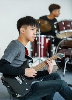 メロディーを演奏する10代のギタリストのポートレートショット。ドラマーをバックにエレキギターを弾く若いミュージシャン。学校の友達と音楽を演奏するプロのジュニア学生