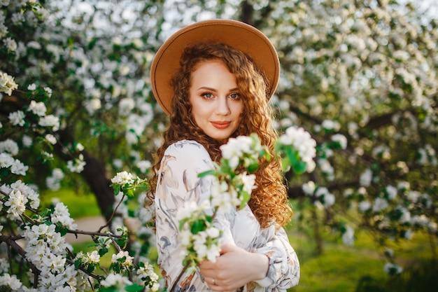 春の公園で咲く白い木の近くの少女のポートレートショット。リンゴの木の花の間に立っているベージュの帽子と白いドレスを着ている女性。春のシーズンのコンセプト。