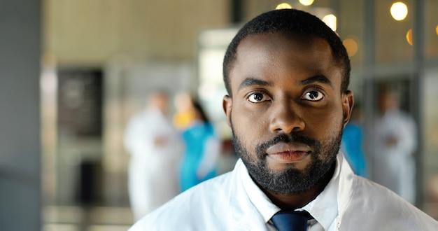 Съемка портрета афро-американского доктора молодого человека смотря камеру и весело улыбаясь. улыбка красивый счастливый мужской врач. медик в белом халате в клинике. в помещении.