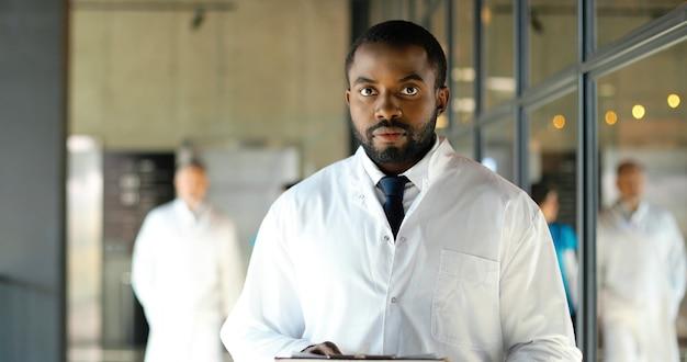 Портрет выстрел афро-американского доктора молодого человека с папкой в руках, глядя на камеру и улыбаясь. красивый счастливый мужчина-врач, работающий в больнице. медик в белом халате в клинике. в помещении.