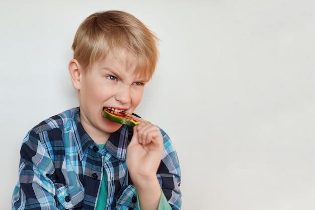 白い壁にロリポップをかむ青い目をした怒っている金髪少年のポートレートショット。かわいい子ポーズ