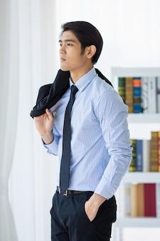Съемка портрета азиатского молодого счастливого успешного библиотекаря снимает черную формальную форму куртки, удерживая ее на плече, стоя на белом фоне книжной полки в одиночестве в библиотеке.