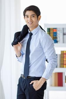 Снимок портрета азиатского молодого счастливого успешного библиотекаря берет черную формальную форму куртки, удерживая ее на плече, стоя смотрит в камеру, улыбаясь на переднем белом фоне книжной полки в одиночестве в библиотеке.