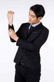 白い背景の前に袖の調整ボタンを笑顔で立っているフォーマルなスーツを着たアジアの若い健康な黒の短い髪のハンサムなホワイトカラーのサラリーマンのポートレートショット。