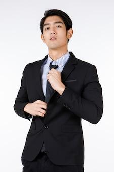 アジアの若い健康な黒の短い髪のハンサムな白い襟のサラリーマンの肖像画のショットは、白い背景の前にカメラを見て両手で調整ネクタイを笑顔で立っているフォーマルなスーツを着ています。