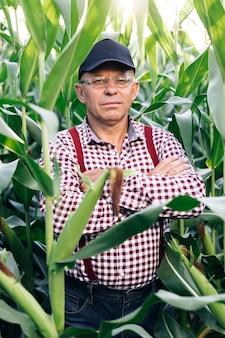 Снимок портрета привлекательного кавказца, стоящего в зеленом кукурузном поле, весело улыбаясь в камеру