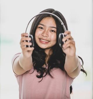 헤드셋으로 음악을 듣고 카메라에 제공하는 매력적인 웃는 어린 소녀 십대의 초상화 샷.