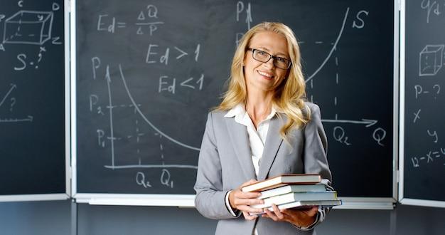 보드에 교실에 서, 카메라에 웃 고 교과서를 들고 아름 다운 백인 여자 선생님의 초상화 샷. 수학 공식 및 그래픽 칠판에 책과 함께 여성 강사.